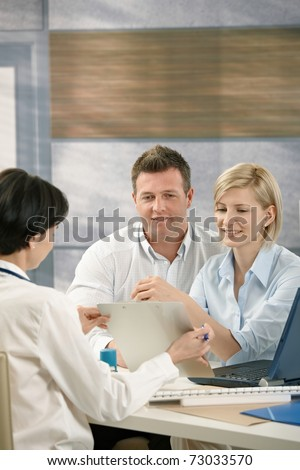 Couple discussing results with physician in doctor's office, smiling.? - stock photo
