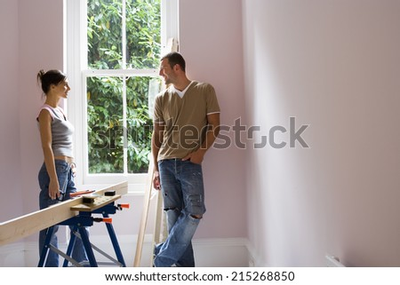 Couple doing DIY at home, standing beside window, woman holding glue gun near timber on workbench - stock photo