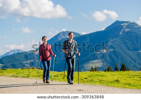 Couple doing Nordic walking exercise in mountains with alpine panorama - stock photo