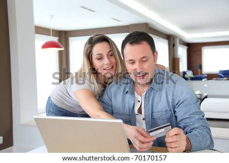 Couple doing online shopping with laptop computer - stock photo