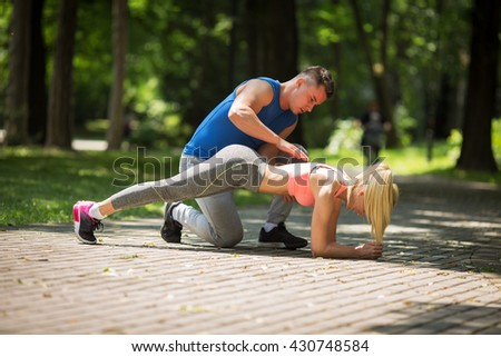 Couple doing push-ups at the park.Workout outdoors.