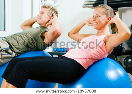 Couple doing situps on a fitness ball as training in the gym - stock photo