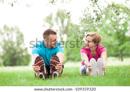 Couple doing stretching exercises in park - stock photo