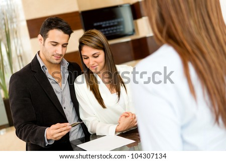 Couple doing the check-in at a hotel paying by credit card - stock photo