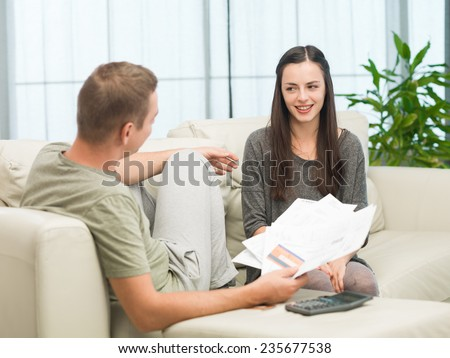 couple doing their accounts at home and laughing - stock photo
