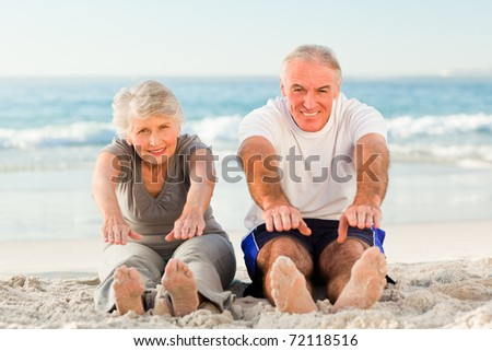 Couple doing their streches at the beach - stock photo