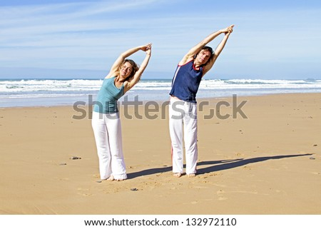 Couple doing yoga excersises at the beach - stock photo