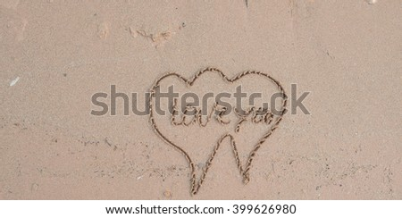 couple drawing a heart on sand