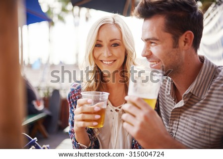 couple drinking beer together at outdoor pub - stock photo