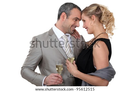 Couple drinking champagne in studio - stock photo
