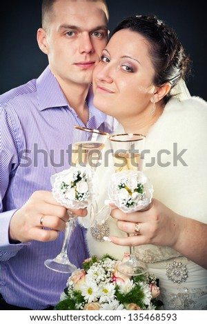 Couple drinking champagne in studio. Bride and groom drinking champagne.