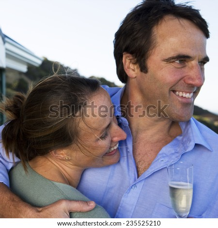 Couple Drinking Champagne on Balcony - stock photo