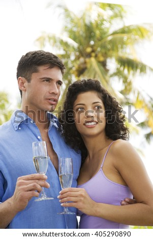 Couple drinking champagne on tropical holiday - stock photo