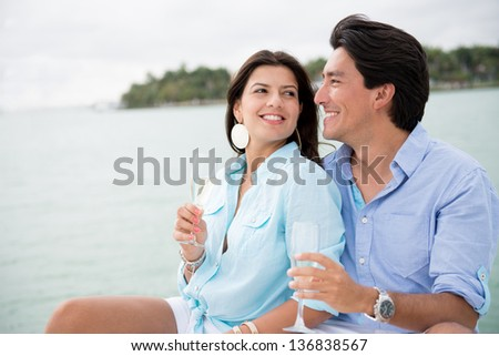 Couple drinking champagne outdoors enjoying their summer holidays