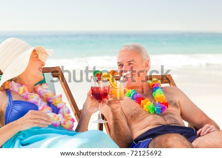Couple drinking cocktails at the beach - stock photo