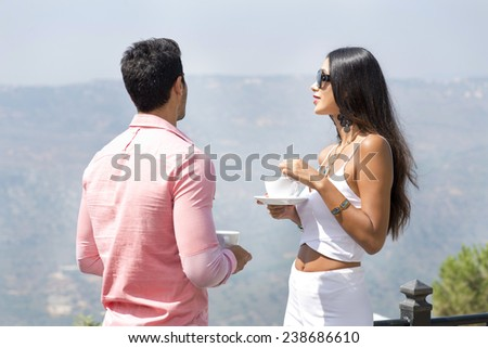 Couple drinking coffee and enjoying the view from hotel balcony - stock photo