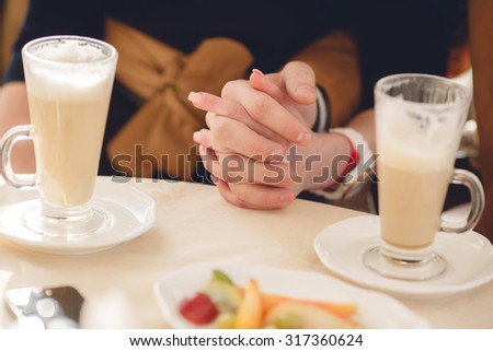 Couple drinking coffee at cafe restaurant man and woman with cup of espresso hot cappuccino on dating. Concept of male and female hands love and coffee. Italian delicious caffeine drink aroma latte - stock photo