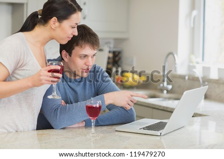 Couple drinking red wine and using laptop in kitchen - stock photo