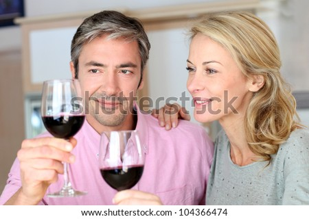 Couple drinking red wine in kitchen - stock photo