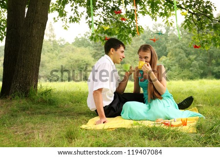 Couple drinking tea in the park under a tree - stock photo