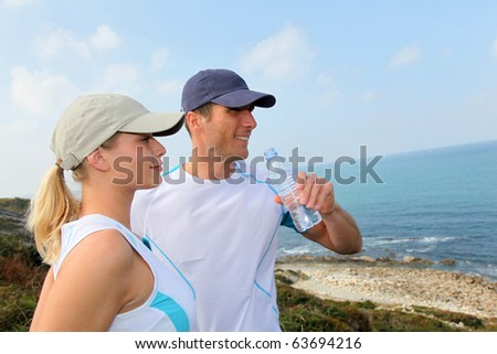 Couple drinking water after exercising - stock photo