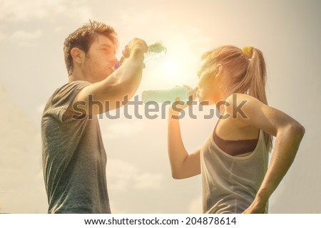 Couple drinking water after workout at sunset - stock photo