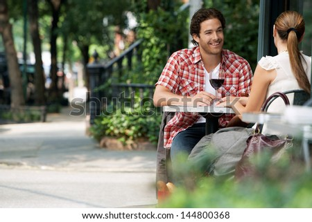 Couple drinking wine at sidewalk cafe - stock photo