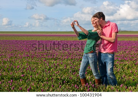 Couple Dutch tourists are taking pictures in the flower fields - stock photo