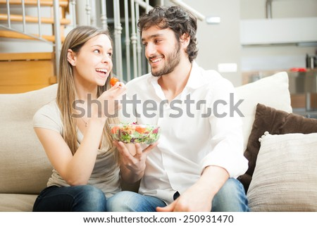Couple eating a salad on the couch - stock photo