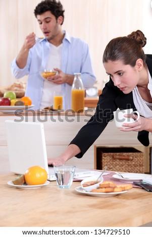 Couple eating breakfast before work - stock photo