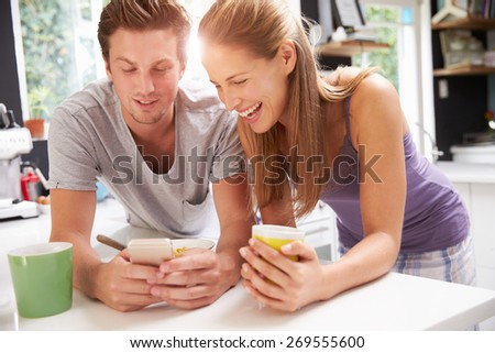Couple Eating Breakfast Whilst Checking Mobile Phone