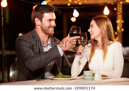 Couple eating dinner at rooftop restuarant - stock photo