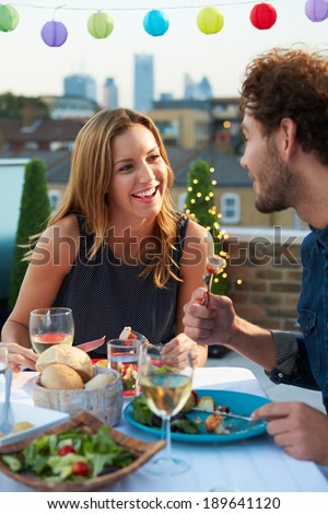 Couple Eating Evening Meal On Rooftop Terrace - stock photo