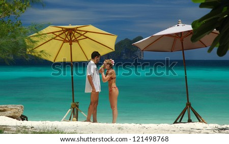 couple eating green apple on the sunny Cote d'Azur on a background of mountains - stock photo