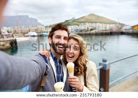 couple eating icecream taking selfie on holiday vacation travel - stock photo