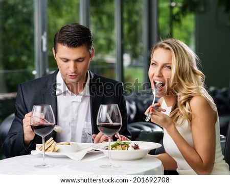Couple eating in restaurant with a red wine  - stock photo