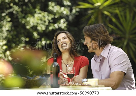 Couple eating in the garden - stock photo