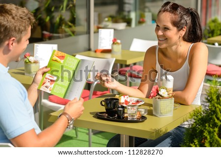 Couple eating looking at menu cafe restaurant smiling woman - stock photo