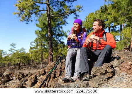 Couple eating lunch taking a break hiking enjoying sandwiches. Hikers living active lifestyle in mountain nature. Woman and man hiker sitting on hike on volcano Teide, Tenerife, Canary Islands, Spain. - stock photo