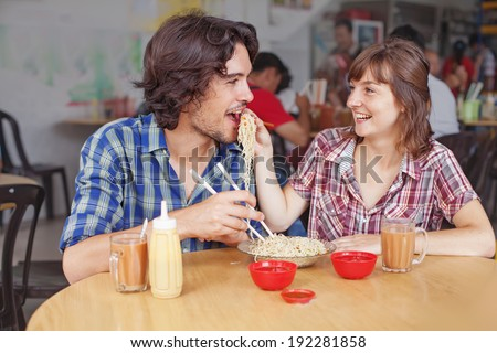 Couple eating noodles in cheap street cafe in Asia - stock photo