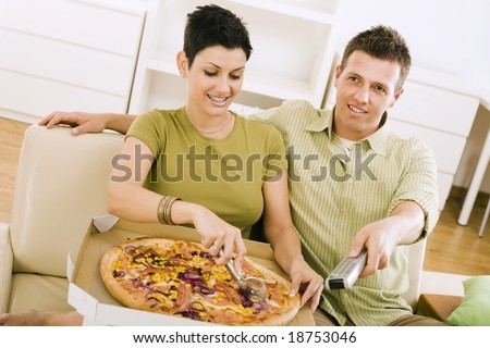 Couple eating pizza and watching TV at home. - stock photo