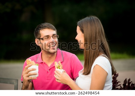 Couple eating sandwich and talking outdoor in nature - stock photo