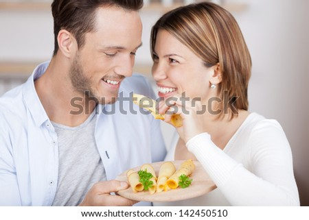 Couple eats some cheese from a variety on plate - stock photo