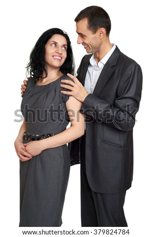 Couple embrace, studio portrait on white. Dressed in black suit.