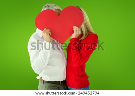 Couple embracing and holding heart over faces against green vignette - stock photo