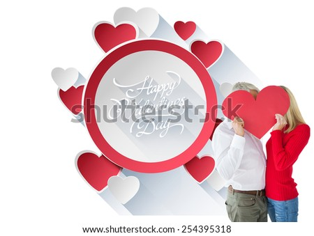 Couple embracing and holding heart over faces against happy valentines day - stock photo