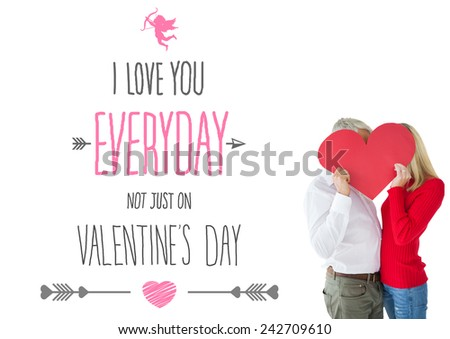 Couple embracing and holding heart over faces against valentines day greeting - stock photo