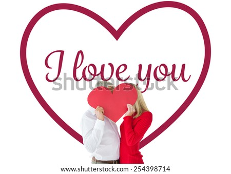 Couple embracing and holding heart over faces against valentines love hearts - stock photo