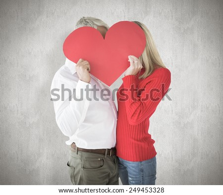 Couple embracing and holding heart over faces against weathered surface - stock photo