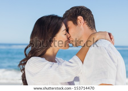 Couple embracing and kissing each other on the beach against ocean - stock photo